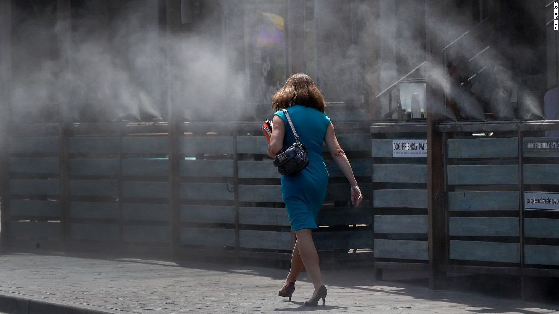 A woman walks through cooling mist in Tempe on June 19.