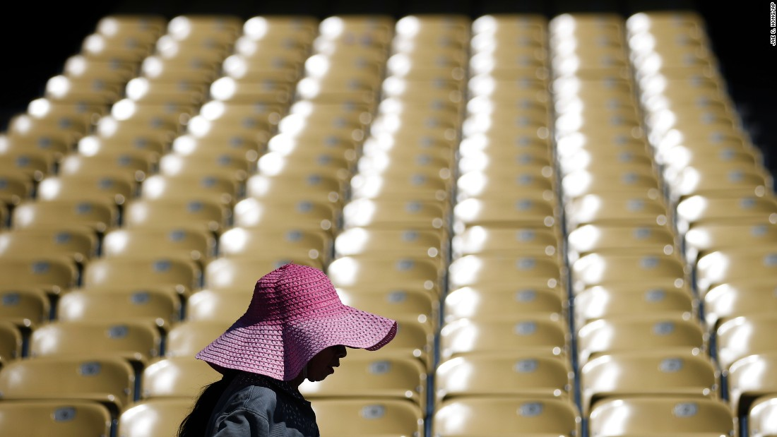 A worker wears a large hat, wet with water, while cleaning seats at Los Angeles' Dodger Stadium on June 19.
