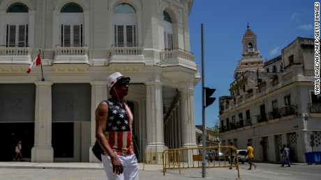 A man wearing a T-shirt with a US flag design walks along a street of Havana on June 16, 2017. US President Donald Trump will deliver a speech in Miami this Friday in which he will present his vision of the rapprochement with Cuba. / AFP PHOTO / Yamil LAGE        (Photo credit should read YAMIL LAGE/AFP/Getty Images)