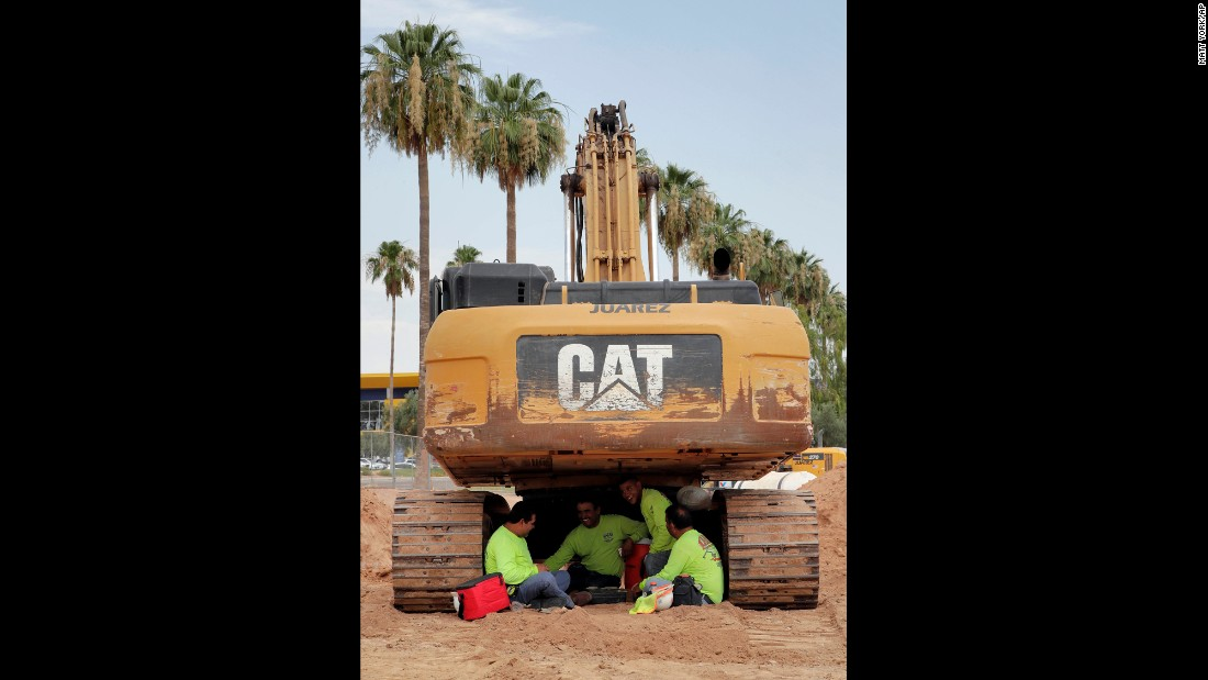 A construction crew sits under their excavator during a break in Tempe on June 20.