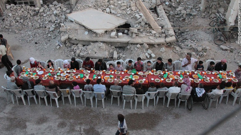 Douma residents gather in a rubble-strewn street to break fast.