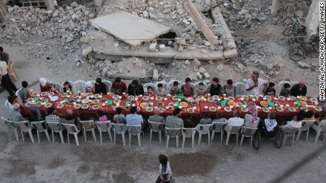 "Syrian residents of the rebel-held town of Douma, on the outskirts of the capital Damascus, break their fast with the ""iftar"" meal on a heavily damaged street on June 18, 2017, during the Muslim holy month of Ramadan.  / AFP PHOTO / Hamza Al-Ajweh        (Photo credit should read HAMZA AL-AJWEH/AFP/Getty Images)"