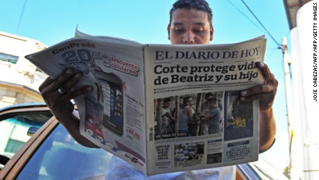 "A man reads a paper headlined: ""Court protects life of Beatriz and child."" Beatriz, a chronically ill Salvadoran woman was denied an abortion in 2013, despite the fact her fetus was unviable."