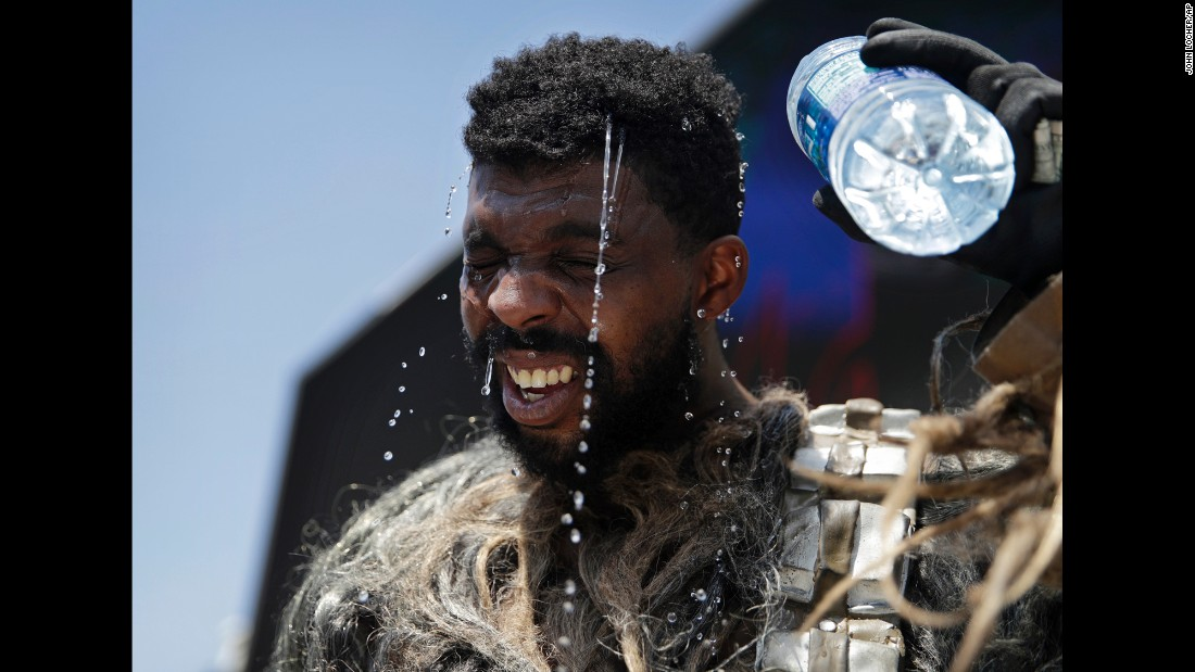 Xaviere Coleman pours water over his head in Las Vegas on Tuesday, June 20. He was wearing a Chewbacca costume to take photographs with tourists on the Strip.