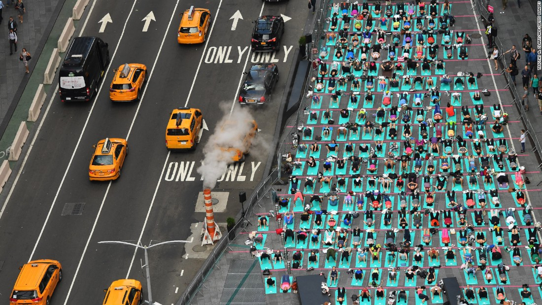 People do yoga in New York's Times Square as part of an annual event celebrating the summer solstice, the longest day of the year, on Wednesday, June 21. It was also International Yoga Day.