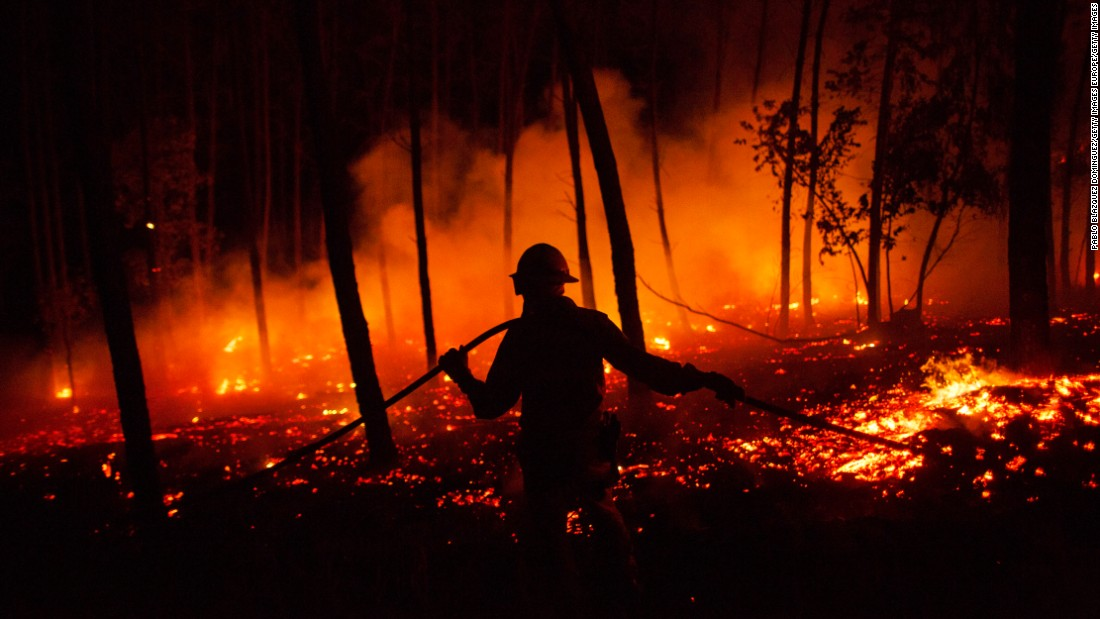 "A firefighter works in a forest in Leiria, Portugal, on Monday, June 19. <a href=""http://www.cnn.com/2017/06/18/europe/portugal-fire/index.html"" target=""_blank"">A raging wildfire</a> has killed at least 62 people and injured dozens more in what officials described as the ""greatest wildfire tragedy of recent years."""