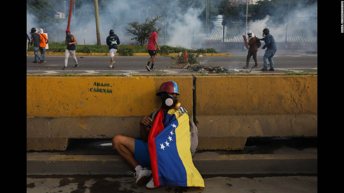 "A protester hides behind a barrier in Caracas, Venezuela, on Thursday, June 22. The country <a href=""http://www.cnn.com/2017/05/09/americas/venezuela-violin-protester/"" target=""_blank"">has witnessed widespread unrest</a> since March 29, when the Venezuelan Supreme Court dissolved Parliament and transferred all legislative powers to itself. Though the decision was reversed three days later, protests continue across the country, which is in the midst of an economic crisis."