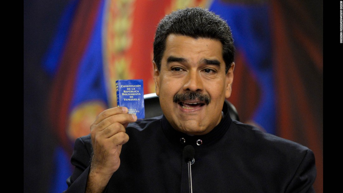 Venezuelan President Nicolas Maduro holds up a copy of the Venezuelan constitution during a news conference at the presidential palace in Caracas on June 22. Maduro has called for changes to the constitution amid the unrest.