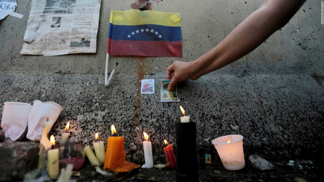 A woman places a prayer card at a makeshift memorial erected where a student was shot and killed during clashes between opposition protesters and Bolivarian National Guard officers in Caracas.