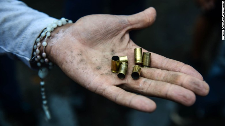 An opposition activist displays bullet shells during an anti-government demonstration on Monday, June 19.