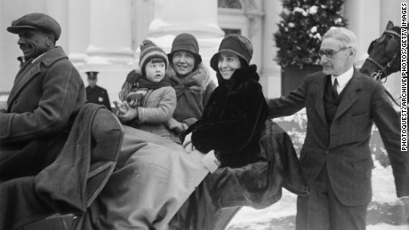 American First Lady Grace Coolidge (nee Goodhue, 1879 - 1957) (center, in dark coat) smiles with unidentified others as she sits in a sleigh, while Chief White House Usher Ike Hoover (1871 - 1933) (right), walks beside them outside the White House, Washington DC, 1929.