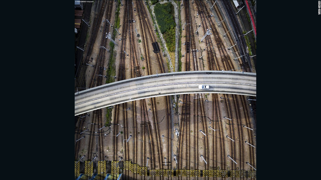 Capturing a flyover intersecting railway tracks, the image reveals the multi-layered transportation networks and sophisticated infrastructural development in Hong Kong which have contributed to city's rapid development.