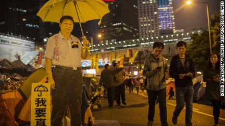 A carboard cutout of Chinese President Xi Jinping holding a yellow umbrella during a protest in Hong Kong.
