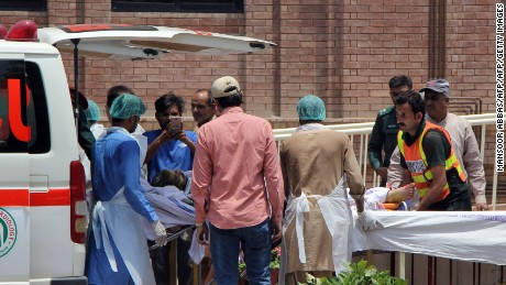 Pakistani paramedics bring a burns victim injured after an oil tanker caught fire following an accident on a highway in central Pakistan to a hospital in Multan on June 25, 2017. At least 123 people were killed and scores injured in a fire that broke out after an oil tanker overturned in central Pakistan early on June 25 and crowds rushed to collect fuel, an official said. / AFP PHOTO / MANSOOR ABBAS        (Photo credit should read MANSOOR ABBAS/AFP/Getty Images)