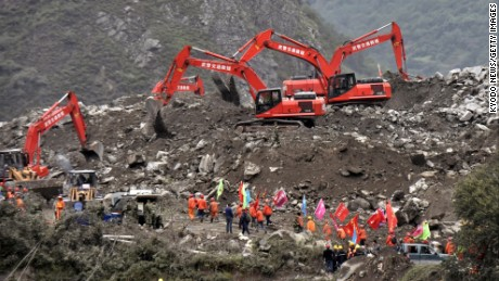 Power shovels continue to search for people missing in a buried village in Sichuan Province, southwestern China on June 25, 2017, after a massive landslide occurred in the morning of the previous day.