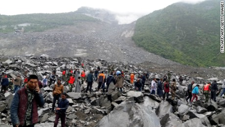TOPSHOT - CORRECTION - Chinese military police and rescue workers are seen at the site of a landslide in in Xinmo village, Diexi town of Maoxian county, Sichuan province on June 24, 2017.  Around 100 people are feared buried after a landslide smashed through their village in southwest China's Sichuan Province early Saturday, local officials said, as they launched an emergency rescue operation. / AFP PHOTO / STR / China OUT / The erroneous mention[s] appearing in the metadata of this photo by STR has been modified in AFP systems in the following manner: [Maoxian] instead of [Maoxiang]. Please immediately remove the erroneous mention[s] from all your online services and delete it (them) from your servers. If you have been authorized by AFP to distribute it (them) to third parties, please ensure that the same actions are carried out by them. Failure to promptly comply with these instructions will entail liability on your part for any continued or post notification usage. Therefore we thank you very much for all your attention and prompt action. We are sorry for the inconvenience this notification may cause and remain at your disposal for any further information you may require.        (Photo credit should read STR/AFP/Getty Images)