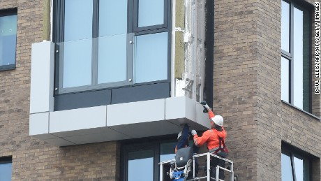 Workers remove panels of external cladding from the facade of a building in the Wythenshawe area of Manchester, northwest England, on June 25, 2017. The Wythenshawe Community Housing Group (WCHG) which run the development the building is part of took the decision, announced in a June 22 statement, to remove 78 feature panels of external cladding from the development after fire safety tests in the wake of the Grenfell Tower fire. Some 34 high-rise buildings in 17 local authorities in England have already failed urgent fire tests conducted after Grenfell, the government announced June 24, raising fears that thousands more may need to leave their homes. / AFP PHOTO / PAUL ELLIS        (Photo credit should read PAUL ELLIS/AFP/Getty Images)
