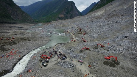 TOPSHOT - Chinese rescuers search for survivors at a landslide area in the village of Xinmo in Maoxian county, China's Sichuan province on June 25, 2017.  Rescuers dug through earth and rocks for a second day on June 25 in an increasingly bleak search for some 118 people still missing after their village in southwest China vanished under a huge landslide. Officials have pulled 15 bodies from the avalanche of rocks that crashed into 62 homes in Xinmo, a once picturesque mountain village nestled by a river in Sichuan province. / AFP PHOTO / STR / China OUT        (Photo credit should read STR/AFP/Getty Images)