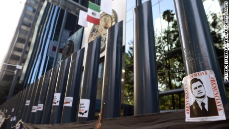Stickers with the image of Mexican President Enrique Pena Nieto are stuck on columns outside the building of the attorney general's office during a protest against alleged government spying on journalists and human rights defenders in Mexico City on June 23, 2017.  Mexican prosecutors said Wednesday they have opened an investigation into allegations the government spied on leading journalists, human rights activists and anti-corruption campaigners. / AFP PHOTO / ALFREDO ESTRELLA        (Photo credit should read ALFREDO ESTRELLA/AFP/Getty Images)