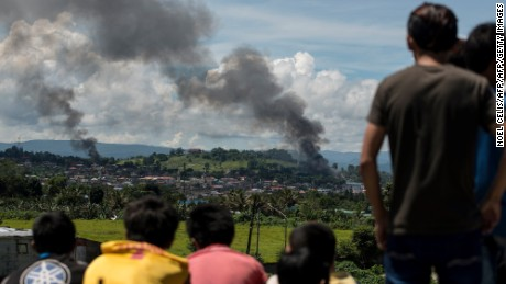 TOPSHOT - People watch as smoke billows from houses after aerial bombings by Philippine Airforce planes on Islamist militant positions in Marawi on the southern island of Mindanao on June 17, 2017.  Philippine troops pounded Islamist militants holding parts of southern Marawi city with air strikes and artillery on June 17 as more soldiers were deployed and the death toll rose to more than 300 after nearly a month of fighting. / AFP PHOTO / Noel CELIS        (Photo credit should read NOEL CELIS/AFP/Getty Images)