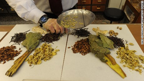 Workers at a traditional chinese medicine store prepare various dried items.