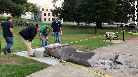 Personnel from the Secretary of State's office inspect the damage to the new Ten Commandments monument outside the state Capitol in Little Rock, Ark., Wednesday morning, June 28, 2017, after someone crashed into it with a vehicle, less than 24 hours after the privately funded monument was installed on the Capitol grounds. Authorities arrested a male suspect. (AP Photo/Jill Zeman Bleed)