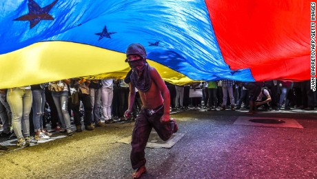 TOPSHOT - A boy runs under a Venezuelan flag during a protest of journalists and media workers against the attacks on journalists, in Caracas on June 27, 2017.  / AFP PHOTO / JUAN BARRETO        (Photo credit should read JUAN BARRETO/AFP/Getty Images)