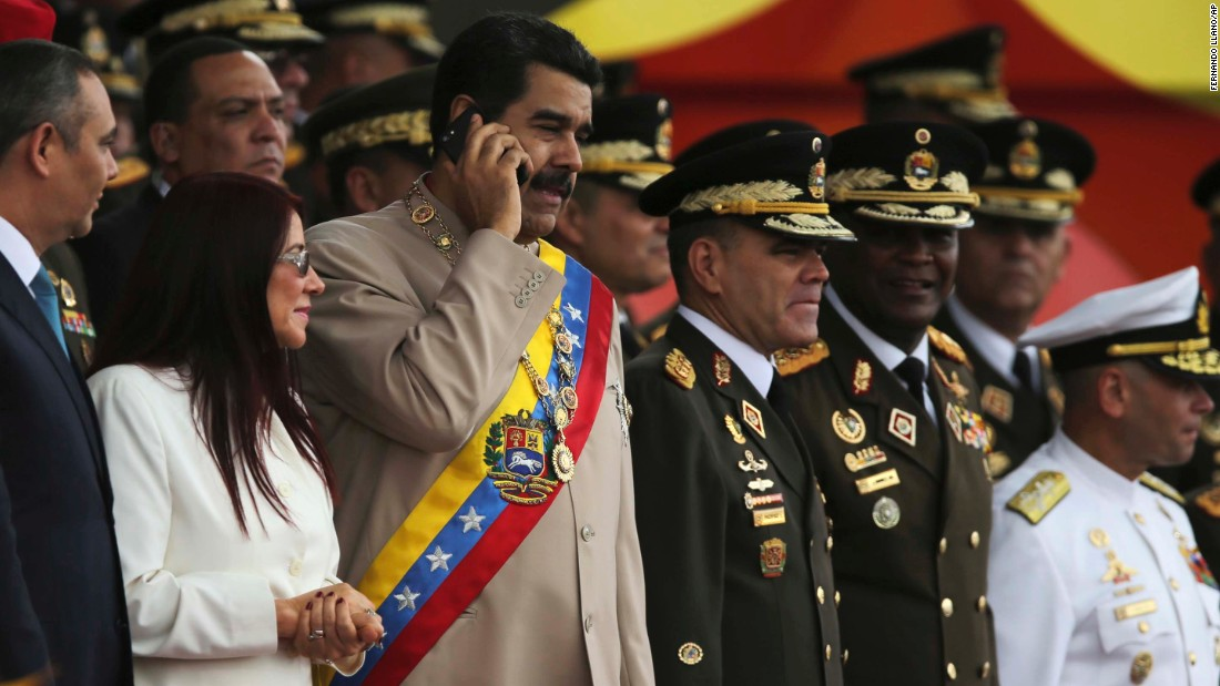 Maduro talks on a cell phone during Army Day celebrations in Caracas on Saturday, June 24. Anti-government protesters have accused Maduro of eroding democracy, and they want him to step down.