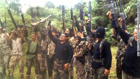 Members of the extremist group, Abu Sayyaf Group (ASG) raise their firearms as they shout slogans in March, 2000 at their hideout in Basilan, 890 kilometers (560 miles) southeast of Manila. Abu Jihad is the masked militant in the foreground of the shot.