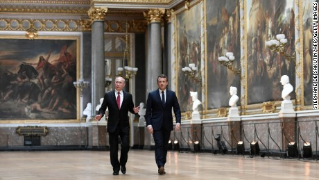 Russian President Vladimir Putin looks around as he walks alongside Macron in the Galerie des Batailles.
