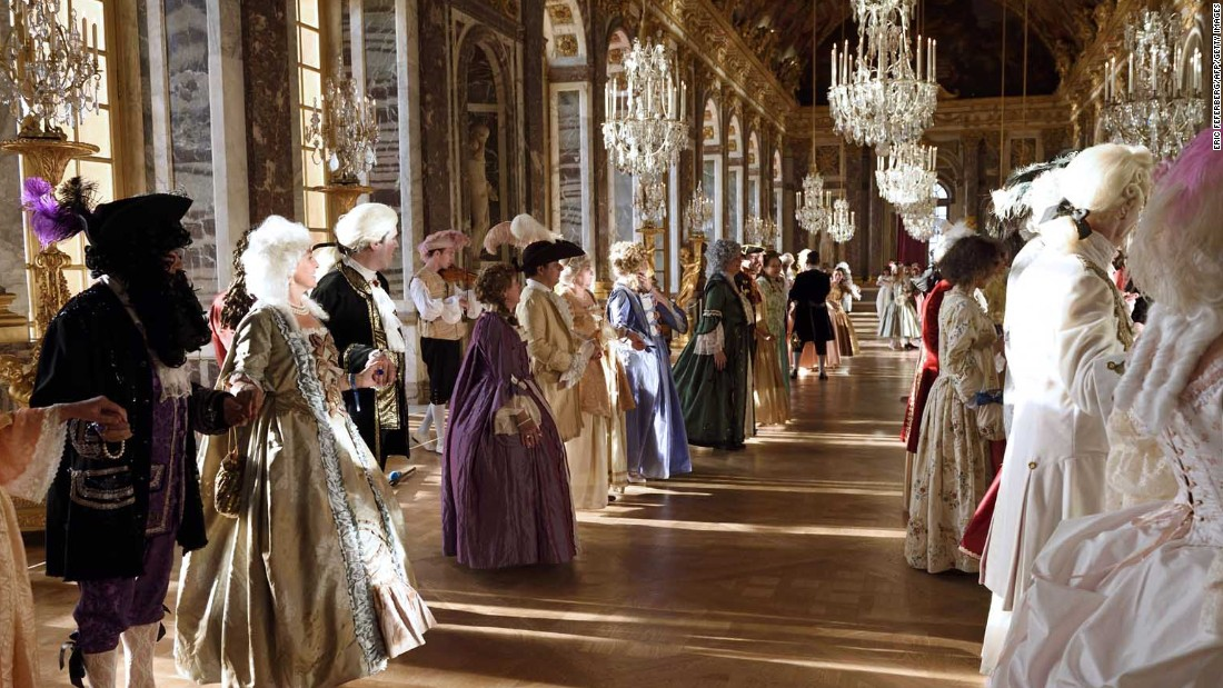 People dressed in period costumes learn dance moves in the Galerie des Glaces, or Hall of Mirrors, at Versailles.