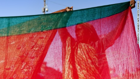 An Indian Hindu devotee dries saris after bathing in the confluence of the Yamuna and Ganges river during the Maha Kumbh Mela festival in Allahabad on February 8, 2013. The Kumbh Mela in the town of Allahabad will see up to 100 million worshippers gather over 55 days to take a ritual bath in the holy waters, believed to cleanse sins and bestow blessings. AFP PHOTO/ ROBERTO SCHMIDT        (Photo credit should read ROBERTO SCHMIDT/AFP/Getty Images)