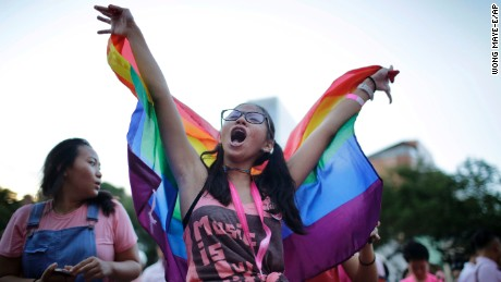 Student Ashleigh Ng, 15, waves a rainbow flag while singing along at a concert during Saturday's Pink Dot gay pride event.
