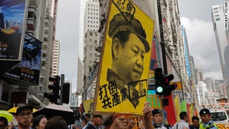 A protester raises a poster with Chinese President Xi Jinping's portrait as thousands march during the annual pro-democracy protest in Hong Kong, Saturday, July 1, 2017.