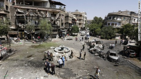 Syrians inspect the site of a suicide bomb attack in the capital's eastern Tahrir Square district on Sunday.