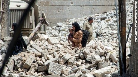TOPSHOT - An Iraqi woman carries a child as she walks through the rubble in the Old City of Mosul on July 2, 2017, during the offensive to retake the city from Islamic State (IS) group fighters. More than eight months since the country's forces launched a gruelling operation to retake Mosul, IS has gone from fully controlling the city to holding a few neighbourhoods on its western side. / AFP PHOTO / Fadel SENNA        (Photo credit should read FADEL SENNA/AFP/Getty Images)