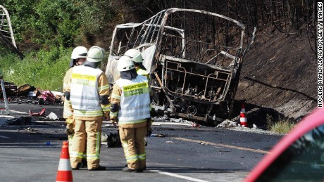 Firefighters work at the scene where a bus burst into flames following a collision with a truck