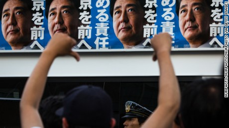 Voters react to Japanese Prime Minister Shinzo Abe's campaign posters during the Tokyo Metropolitan Assembly election.