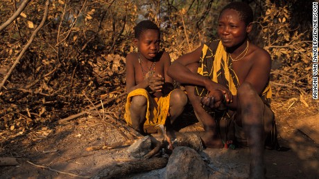Hadza woman and child sitting at a fire, Lake Eyasi, Tanzania.