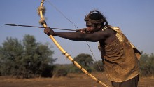Hadza man hunting with bow and arrow, Lake Eyasi, Tanzania. Small tribe of hunter-gatherers also known as the Hadzabe.