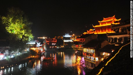 "FENGHUANG TOWNSHIP, CHINA - OCTOBER 20: (CHINA OUT) Lights shine at night along the Tuojiang River at ancient Fenghuang Town on October 20, 2008 in Jishou City of Hunan Province, China. Fenghuang, which means ""Phoenix"" in Chinese, is a well-preserved town of historical and cultural significance. The ancient town is surrounded by mountains with over 100 hundred small rivers and streams criss-crossing the landscape. Most of its residents belong to ethnic minorities, the Tujia and Miao people. (Photo by China Photos/Getty Images)"
