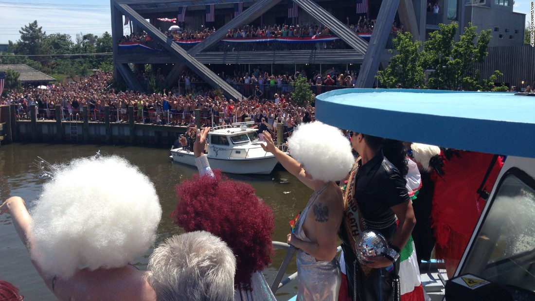 Homecoming Queen Ginger Snap, at center in the red hair, waves to the crowd as a boat approaches the dock. Her entourage was dressed in a Studio 54 theme.