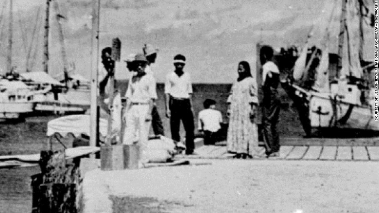 Some experts believe the figure on the far left is Fred Noonan and the person sitting, facing away from the camera, is Amelia Earhart.