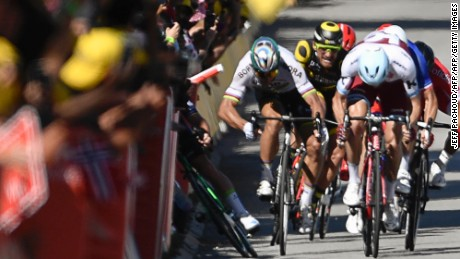 Sagan gives a kick of his elbow and Cavendish (L) falls near the finish line of stage four.