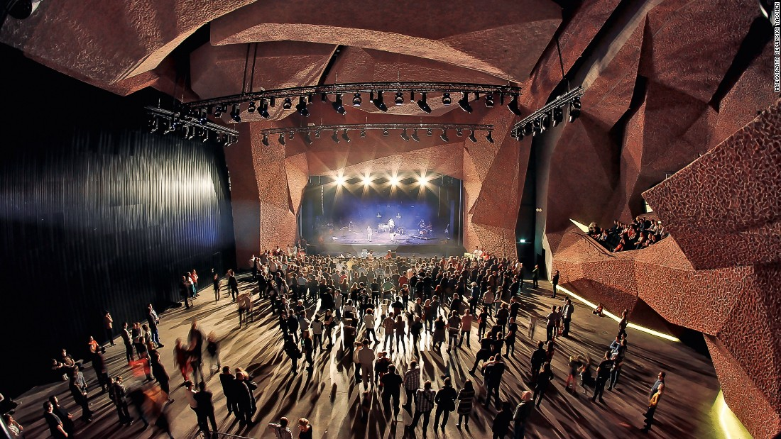 An intimate gig takes place under an umbrella of red brick at the CKK Jordanki Congress and Cultural Center in Torun, Poland. This building takes brick laying to the extreme by using crushed bricks and concrete to create the effect you see inside the building.
