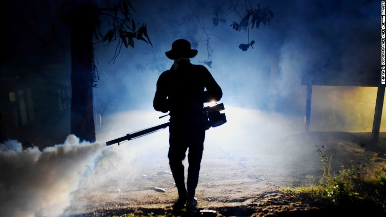 A Sri Lankan health worker sprays a neighborhood with a fog used to ward off mosquitoes in Biyagam, on the outskirts of Colombo in January 2017.