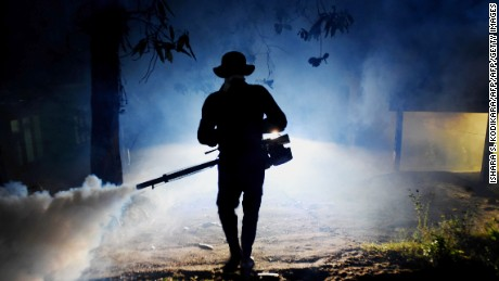 A Sri Lankan health worker sprays a neighborhood with a fog used to ward off mosquitos in January.