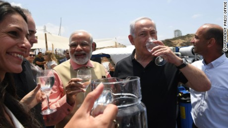 Indian Prime Minister Narendra Modi and Israeli Prime Minister Benjamin Netanyahu enjoy a glass of water during their visit to a mobile desalination unit.