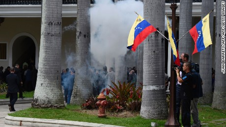Employees of the National Assembly and members of the press run as Supporters of Venezuelan President Nicolas Maduro storm the building in Caracas on July 5, 2017 as opposition deputies hold a special session on Independence Day. A political and economic crisis in the oil-producing country has spawned often violent demonstrations by protesters demanding President Nicolas Maduro's resignation and new elections. The unrest has left 91 people dead since April 1. / AFP PHOTO / Juan BARRETO        (Photo credit should read JUAN BARRETO/AFP/Getty Images)