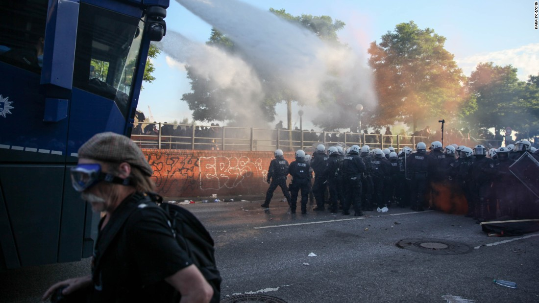 A man wearing protective goggles moves away from officers trying to clear the streets using water cannons.